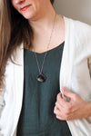 dark blue sparkly crystal talisman necklace on woman in blue top with white sweater