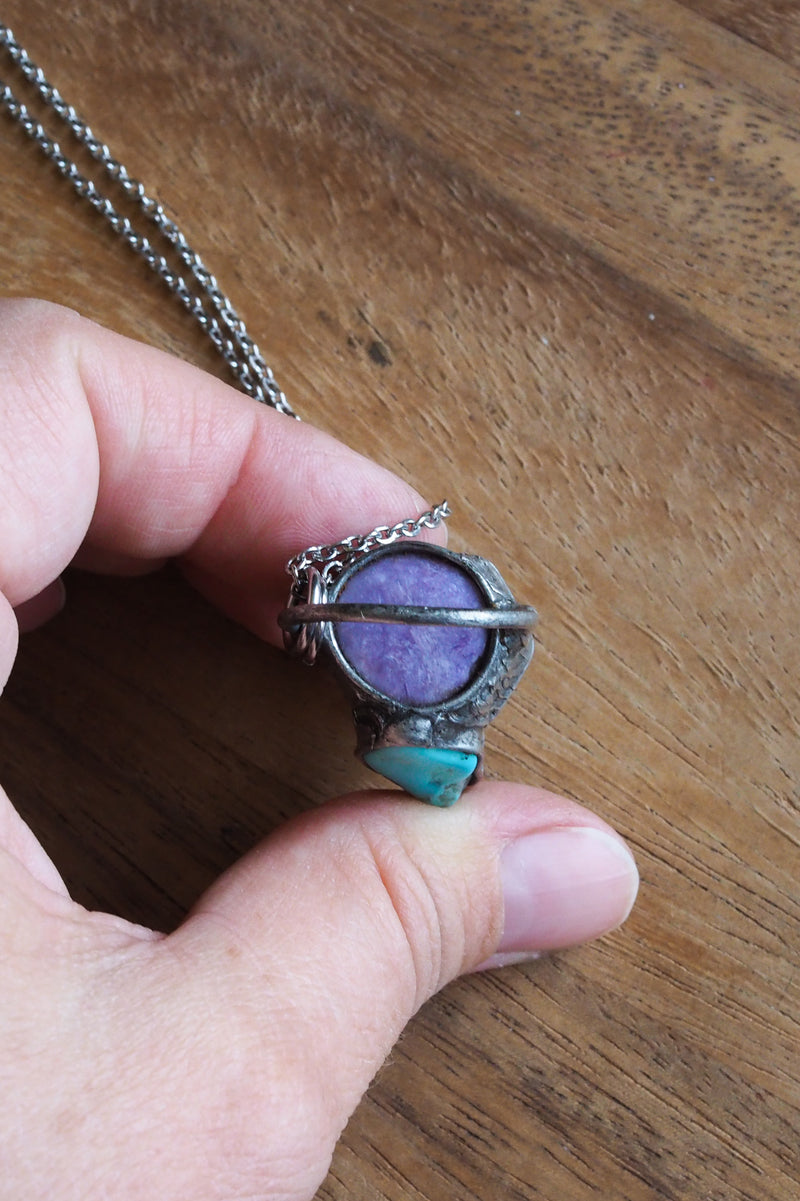 purple and blue gemstone crystal necklace talisman in palm of hand