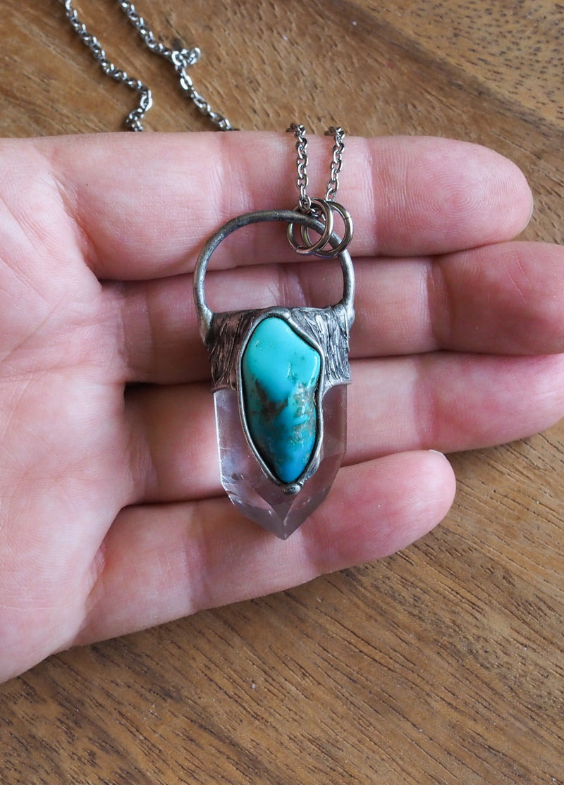 blue gemstone crystal necklace talisman in palm of hand