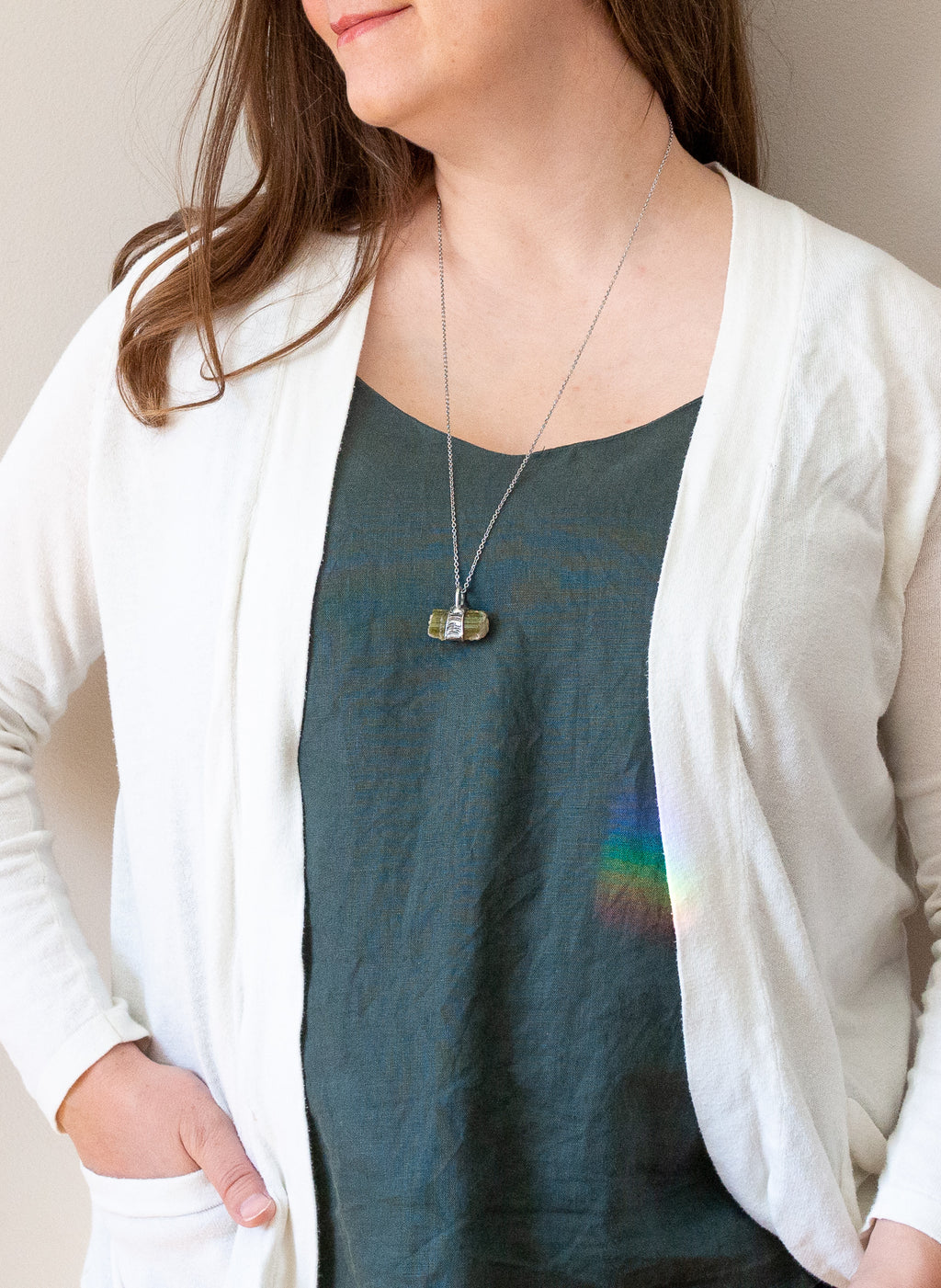 woman in blue top wearing raw green watermelon tourmaline talisman crystal necklace