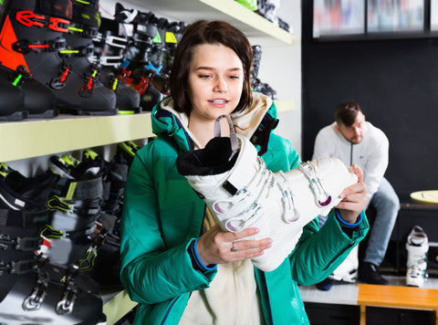Woman chooses new ski boots at a sports equipment store