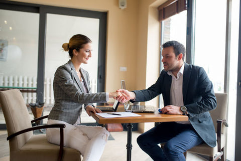 Two people sitting at a table shaking hands