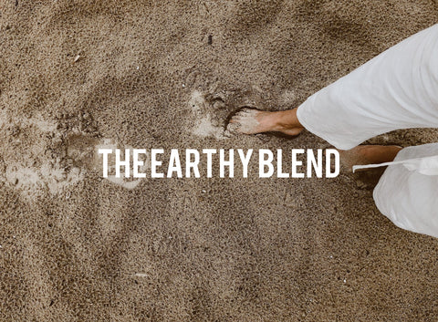 "A picture woman's bare feet on the sand with ""The Earthy Blend"" written on top"