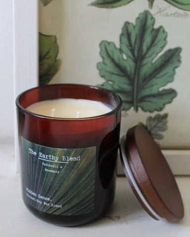 The Earthy Blend 260ml candle in amber glass jar with wooden lid on the side in front of a decorative background.