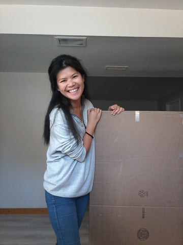 Ellen is smiling while standing next to a large cardboard box.