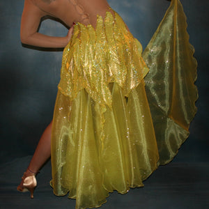 Crystal's Creations close up bottom back view of Yellow Latin/rhythm dress created of yellow hologram lycra, with handcut petal appliques overlaid artistically on nude illusion base,embellished with citrine & jonquil ab Swarovski rhinestones, with converta skirt of yards of glittered organza.
