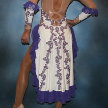 Load image into Gallery viewer, lower back view of White Latin/rhythm dress created with purple lace motifs embellished with crystal Aurora borealis Swarovski rhinestones overlaid on white lycra, and on nude illusion. The finishing touch are ruffles of glitter flecked chiffon.