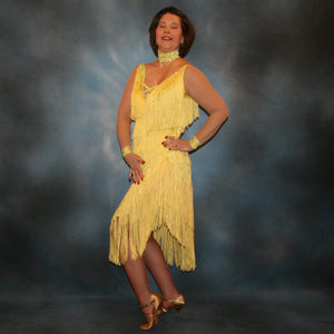 Crystal's Creations side view of Yellow Latin/rhythm fringe dress created in yellow splash metallic lycra with yards of chainette fringe, sheer nude illusion sleeves, embellished with jonquil Swarovski rhinestones.