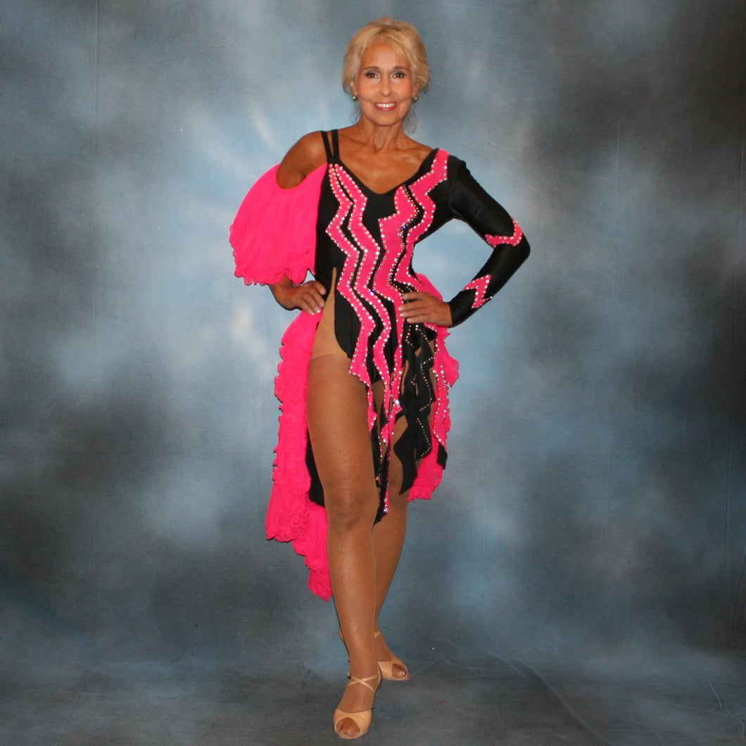 Black Latin/rhythm dance dress with hot pink accents created in black lycra with hot pink hand cut zig zag artwork appliqued detail work & ruffles of hot pink sheer tricot, is embellished with crystal Swarovski rhinestone work.