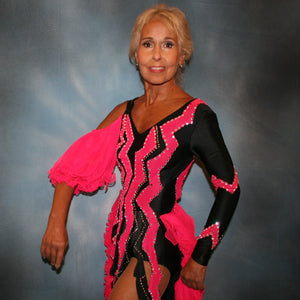 close upper view of Black Latin/rhythm dance dress with hot pink accents created in black lycra with hot pink hand cut zig zag artwork appliqued detail work & ruffles of hot pink sheer tricot, is embellished with crystal Swarovski rhinestone work.