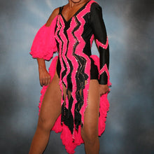 Load image into Gallery viewer, close view of Black Latin/rhythm dance dress with hot pink accents created in black lycra with hot pink hand cut zig zag artwork appliqued detail work & ruffles of hot pink sheer tricot, is embellished with crystal Swarovski rhinestone work.