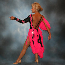 Load image into Gallery viewer, side back view of Black Latin/rhythm dance dress with hot pink accents created in black lycra with hot pink hand cut zig zag artwork appliqued detail work & ruffles of hot pink sheer tricot, is embellished with crystal Swarovski rhinestone work.