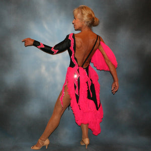 side back view of Black Latin/rhythm dance dress with hot pink accents created in black lycra with hot pink hand cut zig zag artwork appliqued detail work & ruffles of hot pink sheer tricot, is embellished with crystal Swarovski rhinestone work.