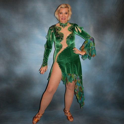 Crystal's Creations Green Latin/rhythm dress was created in luxurious deep emerald green glitter stretch velvet with accent flounces of a green print chiffon. It features nude illusion cutout through the bodice, & is embellished with detailed Swarovski rhinestone work of peridot, emerald & orchid.