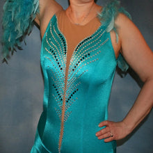 Load image into Gallery viewer, close upper view of Turquoise Latin/rhythm dance dress created in turquoise lycra on nude illusion, is embellished with crystal and jet black Swarovski rhinestones, with chandelle feathers and black spangles. The v styled skirt slits up high on both sides. Matching arm bands complete the look.