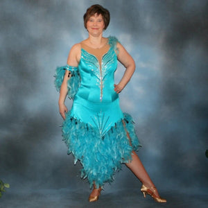 Turquoise Latin/rhythm dance dress created in turquoise lycra on nude illusion, is embellished with crystal and jet black Swarovski rhinestones, with chandelle feathers and black spangles. The v styled skirt slits up high on both sides. Matching arm bands complete the look.
