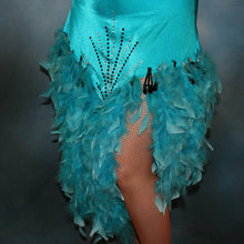 Load image into Gallery viewer, lower view of Turquoise Latin/rhythm dance dress created in turquoise lycra on nude illusion, is embellished with crystal and jet black Swarovski rhinestones, with chandelle feathers and black spangles. The v styled skirt slits up high on both sides. Matching arm bands complete the look.