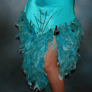 lower view of Turquoise Latin/rhythm dance dress created in turquoise lycra on nude illusion, is embellished with crystal and jet black Swarovski rhinestones, with chandelle feathers and black spangles. The v styled skirt slits up high on both sides. Matching arm bands complete the look.