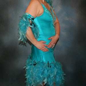 close side view of Turquoise Latin/rhythm dance dress created in turquoise lycra on nude illusion, is embellished with crystal and jet black Swarovski rhinestones, with chandelle feathers and black spangles. The v styled skirt slits up high on both sides. Matching arm bands complete the look.