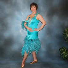 Load image into Gallery viewer, side view of Turquoise Latin/rhythm dance dress created in turquoise lycra on nude illusion, is embellished with crystal and jet black Swarovski rhinestones, with chandelle feathers and black spangles. The v styled skirt slits up high on both sides. Matching arm bands complete the look.