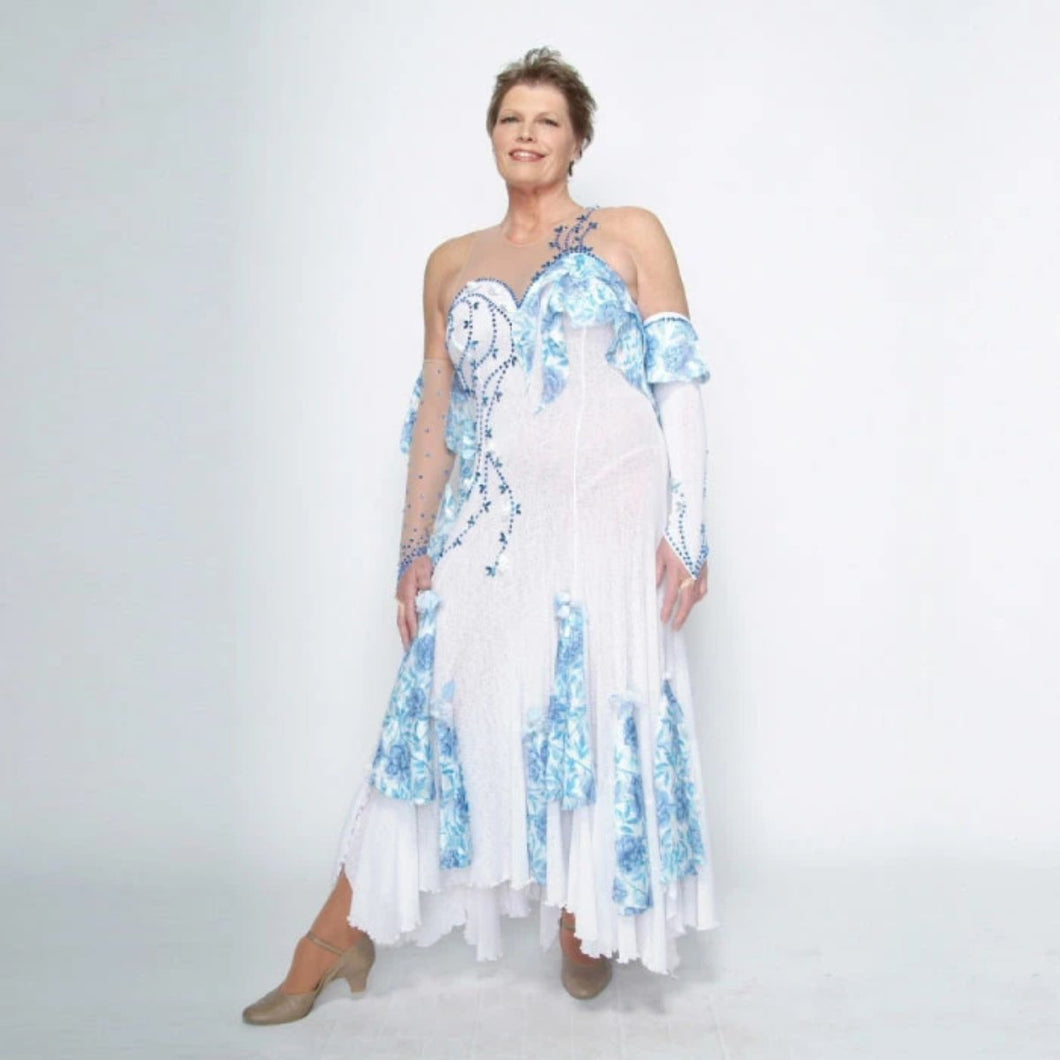 White ballroom dress with blue accents was created on nude illusion of a soft white knit with flounce accents of sky blue & white floral print satin, embellished with sapphire Swarovski stonework & miniature white silk roses.