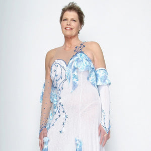 close upper view of White ballroom dress with blue accents was created on nude illusion of a soft white knit with flounce accents of sky blue & white floral print satin, embellished with sapphire Swarovski stonework & miniature white silk roses.
