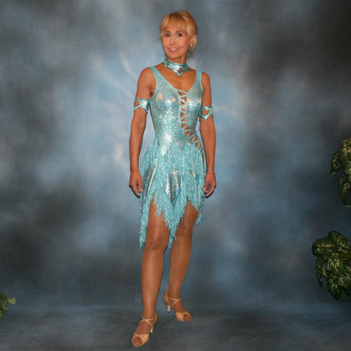 Crystal's Creations Light turquoise Latin/rhythm dance dress created in turquoise hologram metallic lycra with hologram sequined fringe, is embellished with blue zircon Swarovski rhinestones, & features cutout detailing.