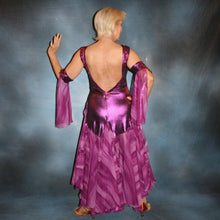 Load image into Gallery viewer, Crystal's Creations back view of Purple/plum ballroom dress created of rich & luxurious plum metallic slinky ballroom dance dress with yards & yards of print chiffon… embellished with fuchsia Swarovski rhinestones… along with hand beading of bicone & teardrop Swarovski beads