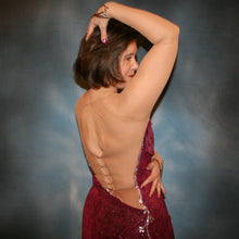 Load image into Gallery viewer, close back view of Burgundy Latin/rhythm dress created of burgundy glitter slinky with subtle reptilia print on a nude illusion base with chainette fringe, embellished with crystal & burgundy Swarovski rhinestone work.
