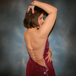 close back view of Burgundy Latin/rhythm dress created of burgundy glitter slinky with subtle reptilia print on a nude illusion base with chainette fringe, embellished with crystal & burgundy Swarovski rhinestone work.