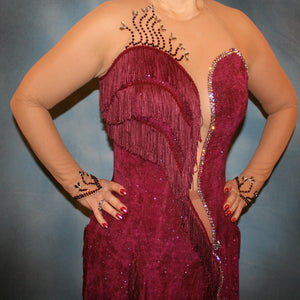 close front view of Burgundy Latin/rhythm dress created of burgundy glitter slinky with subtle reptilia print on a nude illusion base with chainette fringe, embellished with crystal & burgundy Swarovski rhinestone work.