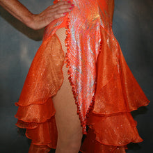 Load image into Gallery viewer, Crystal's Creations bottom view of details on Orange Latin/rhythm dress was created in orange & silver metallic print lycra with oodles of glitter organza flounces & accents, has back strap detailing, embellished with extensive Swarovski hand beading & has matching Swarovski hand beaded neckpiece.