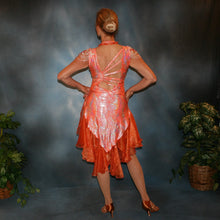 Load image into Gallery viewer, Crystal's Creations back view of Orange Latin/rhythm dress was created in orange & silver metallic print lycra with oodles of glitter organza flounces & accents, has back strap detailing, embellished with extensive Swarovski hand beading & has matching Swarovski hand beaded neckpiece.