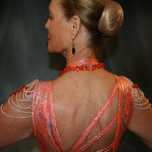 Load image into Gallery viewer, Crystal's Creations close up back view of Orange Latin/rhythm dress was created in orange & silver metallic print lycra with oodles of glitter organza flounces & accents, has back strap detailing, embellished with extensive Swarovski hand beading & has matching Swarovski hand beaded neckpiece.