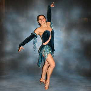 Crystal's Creations Latin/rhythm dance dress created of deep turquoise sea blue glitter stretch velvet fabric on nude illusion base is embellished with turquoise Swarovski rhinestones stones & lots of hand beading with sequin paillette bangles.
