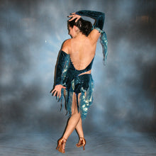 Load image into Gallery viewer, Crystal's Creations back view of Latin/rhythm dance dress created of deep turquoise sea blue glitter stretch velvet fabric on nude illusion base is embellished with turquoise Swarovski rhinestones stones & lots of hand beading with sequin paillette bangles.