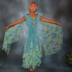Turquoise ballroom dress of turquoise glitter slinky features lattice work detailing with yards & yards of print chiffon, enhanced with velveteen flowers plus aquamarine Swarovski rhinestones, hand beading on shoulder detailing... with detachable floats.