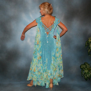 Crystal's Creations back view of Turquoise ballroom dress of turquoise glitter slinky features lattice work detailing with yards & yards of print chiffon, enhanced with velveteen flowers plus aquamarine Swarovski rhinestones, hand beading on shoulder detailing... with detachable floats.