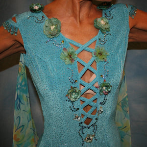 Crystal's Creations close up view of Turquoise ballroom dress of turquoise glitter slinky features lattice work detailing with yards & yards of print chiffon, enhanced with velveteen flowers plus aquamarine Swarovski rhinestones, hand beading on shoulder detailing... with detachable floats.