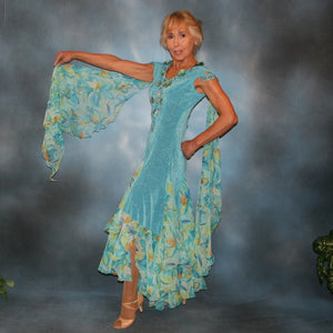 Crystal's Creations side view of Turquoise ballroom dress of turquoise glitter slinky features lattice work detailing with yards & yards of print chiffon, enhanced with velveteen flowers plus aquamarine Swarovski rhinestones, hand beading on shoulder detailing... with detachable floats.
