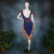 Load image into Gallery viewer, Crystal's Creations back view of Converta ballroom dress featuring a Latin/rhythm dress created in luxurious deep perwinkle solid slinky with lots of flounces in accents of a floral chiffon in yellow with pinks & purples