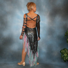 Load image into Gallery viewer, back view of Striking iridescent black Latin/rhythm dress of iridescent splash lycra fabric has tones of aqua and orchid throughout. The angle style skirt has wispy founces of aqua and orchid chiffon and drips with hand beading and aqua bangles. It also features sexy strap detailing down one arm, in open torso area and back. The other sheer sleeve is topped with a cap of hand beading and bangles.