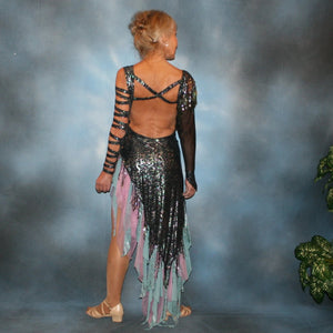 back view of Striking iridescent black Latin/rhythm dress of iridescent splash lycra fabric has tones of aqua and orchid throughout. The angle style skirt has wispy founces of aqua and orchid chiffon and drips with hand beading and aqua bangles. It also features sexy strap detailing down one arm, in open torso area and back. The other sheer sleeve is topped with a cap of hand beading and bangles.