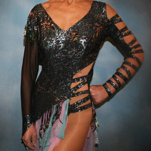 close upper view of Striking iridescent black Latin/rhythm dress of iridescent splash lycra fabric has tones of aqua and orchid throughout. The angle style skirt has wispy founces of aqua and orchid chiffon and drips with hand beading and aqua bangles. It also features sexy strap detailing down one arm, in open torso area and back. The other sheer sleeve is topped with a cap of hand beading and bangles.