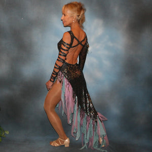 side view of Striking iridescent black Latin/rhythm dress of iridescent splash lycra fabric has tones of aqua and orchid throughout. The angle style skirt has wispy founces of aqua and orchid chiffon and drips with hand beading and aqua bangles. It also features sexy strap detailing down one arm, in open torso area and back. The other sheer sleeve is topped with a cap of hand beading and bangles.
