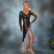 Load image into Gallery viewer, right side view of Striking iridescent black Latin/rhythm dress of iridescent splash lycra fabric has tones of aqua and orchid throughout. The angle style skirt has wispy founces of aqua and orchid chiffon and drips with hand beading and aqua bangles. It also features sexy strap detailing down one arm, in open torso area and back. The other sheer sleeve is topped with a cap of hand beading and bangles.