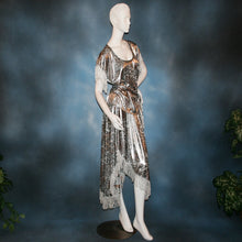 Load image into Gallery viewer, side view of Silver two panel Latin/rhythm skirt & top that has hand beading on neck edge of textured silver beads, with metallic fringe, was created of a leopard print knit with silver metallic on one side.