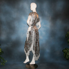Load image into Gallery viewer, Crystal's Creations side view of Silver two panel Latin/rhythm skirt & top that has hand beading on neck edge of textured silver beads, with metallic fringe, was created of a leopard print knit with silver metallic on one side.