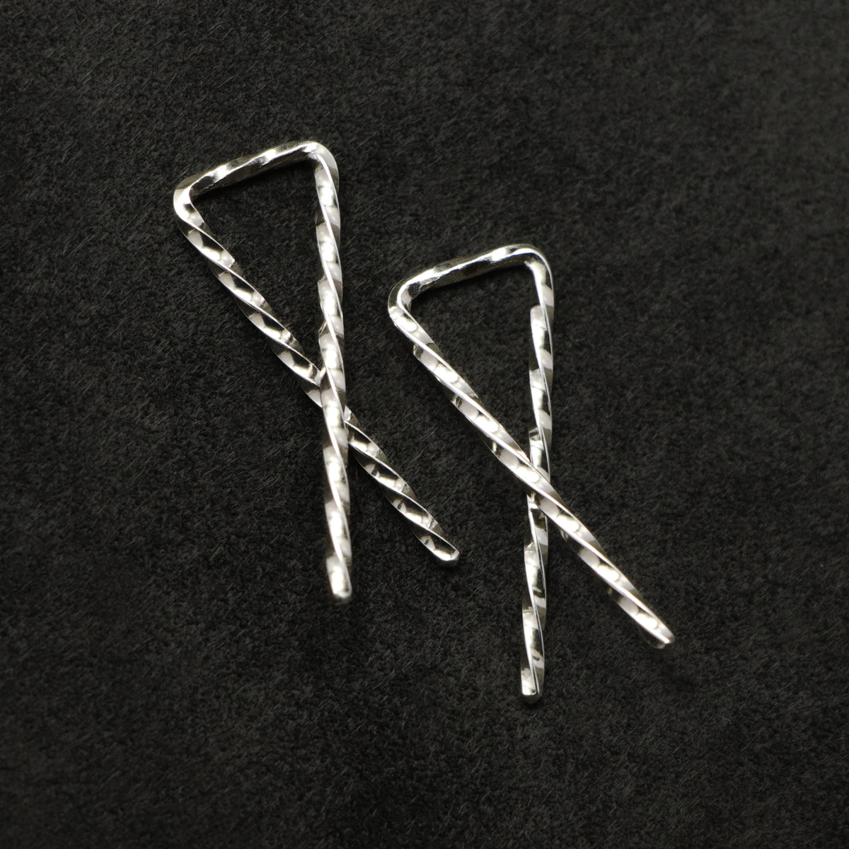 Detail view of Sibling Ribbons in Sterling Silver earring representing we are all brothers and sisters by Caps Brothers