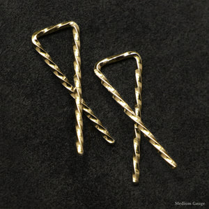 Detail view of 18K Yellow Gold Sibling Ribbons Twisted Earrings representing we are all brothers and sisters by Caps Brothers